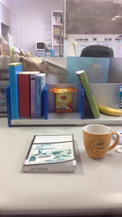En kopp ved siden av en bok på en lesesal.