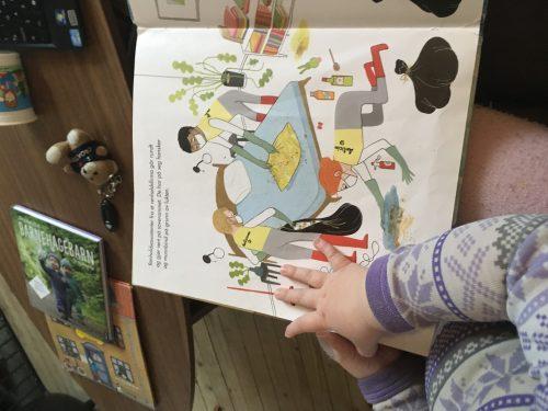 En barneånd holder å en bokside som viser et rengjøringsteam med masker og gule frakker fjerne bæsj fra soverom