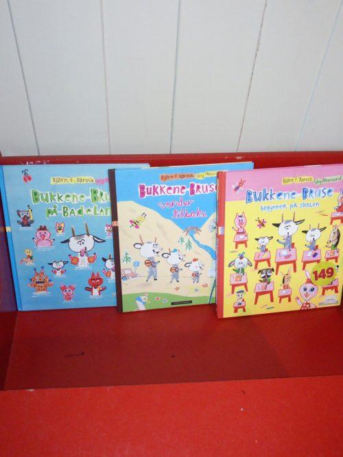 Rød benk med forsiden av bøkene om bukkene bruse står på. En i basseng, en på fjell og en rosa med skole